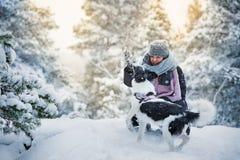 Donna che gioca con il cane in foresta nevosa immagini stock