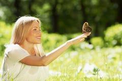 Donna che gioca con la farfalla immagine stock