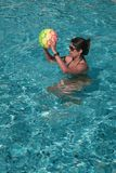 Donna che gioca con la palla in una piscina fotografia stock