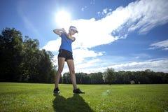Donna che gioca golf sul campo Fotografia Stock