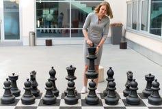 Donna che gioca il gioco di scacchi Immagine Stock