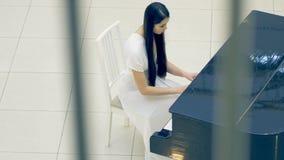 Donna che gioca il piano in vestito bianco stock footage