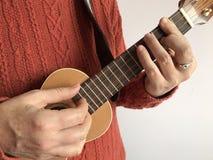 Donna che gioca le ukulele del soprano all'interno fotografie stock