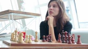 Donna che gioca posizione dell'interno e di pensiero di scacchi, movimento di conquista del ritrovamento, alesaggio di strategia stock footage