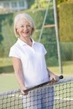 Donna che gioca tennis e sorridere Immagini Stock