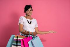 Donna che giudica i sacchetti della spesa e mano che presentano gesto immagine stock libera da diritti