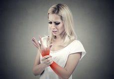 Donna che giudica la sua posizione dolorosa di dolore di distorsione del polso indicata dal punto rosso fotografia stock