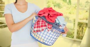 Donna che giudica un canestro pieno dei vestiti a casa Immagine Stock