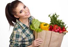 Donna che giudica un sacchetto della spesa pieno di alimento fresco immagine stock libera da diritti