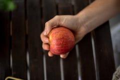 Donna che giudica una mela disponibila fotografia stock