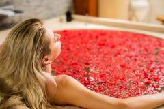 Donna che gode del bagno rosso del fiore Fotografia Stock