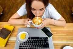 Donna che gode del cappuccino che si siede con il computer portatile Immagini Stock