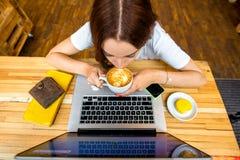 Donna che gode del cappuccino che si siede con il computer portatile Immagine Stock