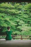 Donna che gode del giardino giapponese da un terrazzo del tempio, Kyoto, Giappone Fotografie Stock