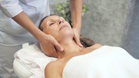 Donna che gode del massaggio del collo nel centro della stazione termale della località di soggiorno archivi video
