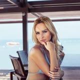 Donna che gode del sole di estate che si siede nella barra Bello giovane modello del bikini fotografia stock