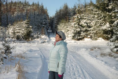 Donna che gode del sole in foresta nell'inverno immagini stock libere da diritti