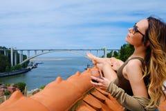 Donna che gode del sunbath con vetro di porto sul tetto sul fondo del ponte del fiume Fotografia Stock Libera da Diritti