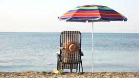 Donna che gode del sunbath di mattina vicino alla spiaggia video d archivio