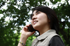 Donna che gode della conversazione su un telefono delle cellule Fotografia Stock