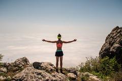 Donna che gode della natura nelle montagne e che considera cielo con le mani sollevate Fotografia Stock Libera da Diritti