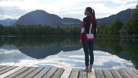 Donna che gode della vista delle montagne e del lago video d archivio