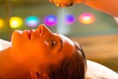 Donna che gode di un massaggio dell'olio di Ayurveda fotografia stock libera da diritti
