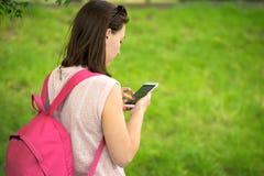 Donna che gode di un telefono in parco Immagini Stock