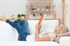 Donna che gode leggendo un libro a casa Fotografia Stock