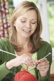 Donna che gode tricottando indumento a casa fotografia stock
