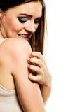 Donna che graffia il suo braccio Fotografie Stock Libere da Diritti