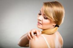 Donna che graffia il suo braccio che prude con l'eruzione di allergia Immagine Stock