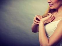 Donna che graffia il suo polso che prude con l'eruzione di allergia fotografie stock libere da diritti