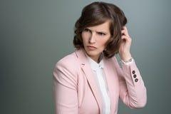 Donna che graffia la sua testa con un aggrottare le sopracciglia imbarazzato Fotografia Stock Libera da Diritti