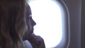 Donna che guarda all'aeroplano del passeggero di volo della finestra Bella ragazza che guarda alla finestra degli aerei mentre vo archivi video