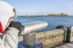 Donna che guarda all'isola di Dalkey dal binocolo Immagini Stock Libere da Diritti
