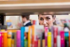 Donna che guarda attraverso lo scaffale dei libri che scelgono volume per leggere Immagini Stock