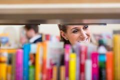 Donna che guarda attraverso lo scaffale dei libri che scelgono volume per leggere Fotografia Stock Libera da Diritti