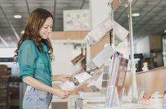 Donna che guarda catalogo nel deposito del bagno Fotografie Stock