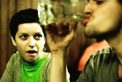 Donna che guarda con aria sciocca a bere dell'uomo immagine stock libera da diritti