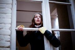 Donna che guarda con la finestra ed il timore di qualcosa Immagine Stock