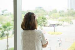 Donna che guarda fuori dalla sua finestra dell'ufficio fotografia stock