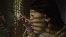 Donna che guarda fuori la finestra attraverso i ciechi alla via, spiante