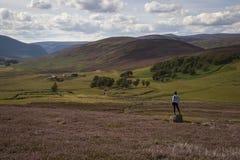 Donna che guarda fuori sopra un paesaggio scozzese immagini stock