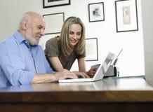 Donna che guarda il computer portatile maturo di uso dell'uomo a casa fotografia stock libera da diritti
