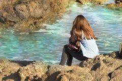 Donna che guarda il mare che si siede retrovisione sola e immagini stock libere da diritti