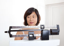 Donna che guarda il suo peso sulla scala del peso Immagine Stock Libera da Diritti