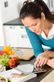 Donna che guarda le verdure della cucina di ricetta della lettura della compressa Immagine Stock