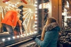Donna che guarda nella finestra del negozio sui regali di compera di Natale Fotografia Stock