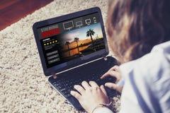 Donna che guarda scorrendo la serie in un computer portatile Fotografia Stock